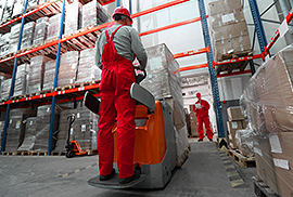 Two warehouse workers moving boxes
